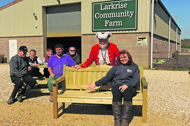 This Is Wiltshire: They're sitting pretty at Larkrise with their new seats. At front is the farm's manager Wedy Self while some of her colleagues take a rest on a picnic table also given by Mr Heeks, standing