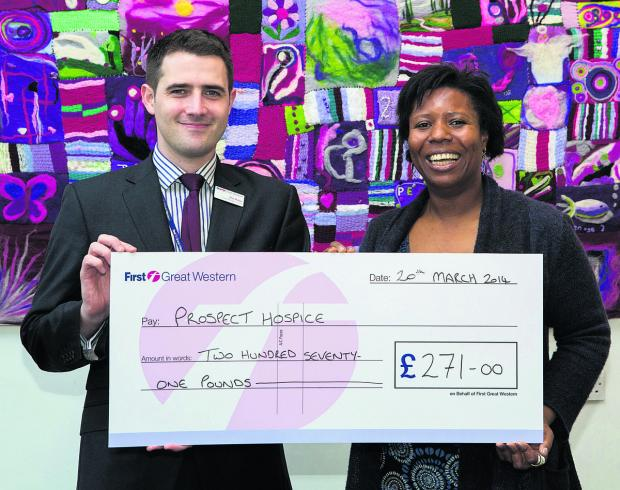 This Is Wiltshire: Rob Mullen, First Great Western's general manager for the Central Region, presents a cheque for £271 to Gifty Tawiah, Community Fund Raiser for Prospect Hospice