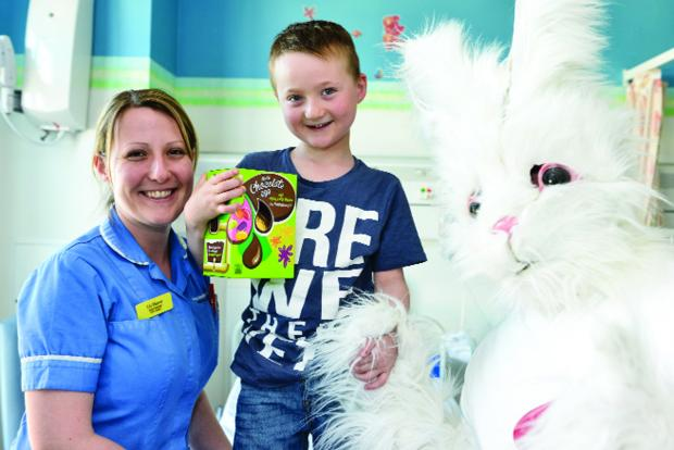 This Is Wiltshire: Ben Osmond gets his Easter egg from the bunny. Pictured with him is his mum Liz Mawer, a nurse in the GMH eye clinic