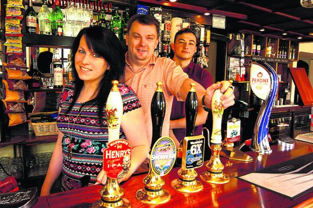 This Is Wiltshire: From left, Charlotte Goddard, Monty Hadrill and Grant Angell behind the pumps at The Bell By The Green                              (PM1181) By PAUL MORRIS