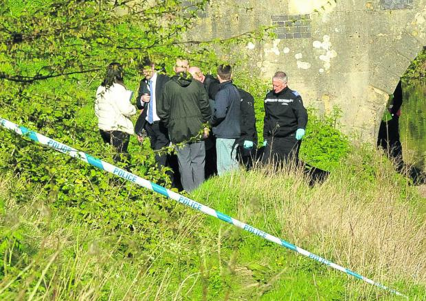 This Is Wiltshire: Police carry the body from the canal