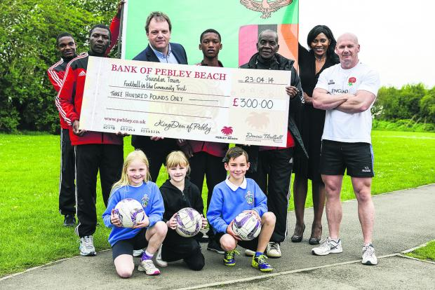 This Is Wiltshire: Football coaches from Zambia visited Robert Le Kyng Primary School to talk about the links with Swindon and Football. Pictured at a cheque presentation from Pebley Beach for £300 to the Football in the Community Trust are (front kneeling) Amelie, Jorja,