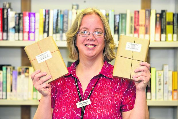 This Is Wiltshire: Great Western Hospital head librarian Sam Burgess with mystery books to encourage people to read different authors