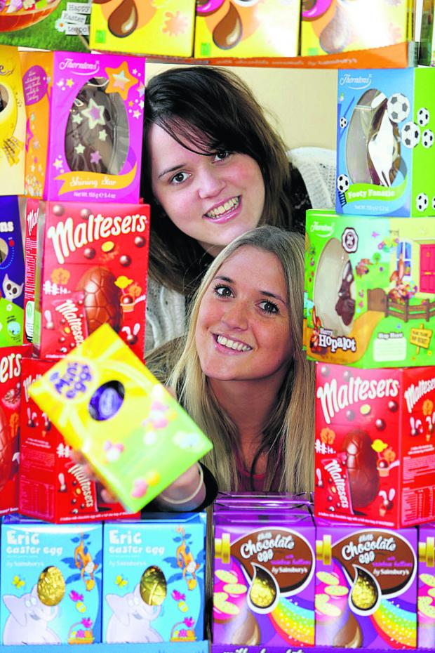 This Is Wiltshire: Amy Francombe, top, with Nichola Fisher from Reed consultancy pictured with some Easter eggs donated in aid of Prospect Hospice