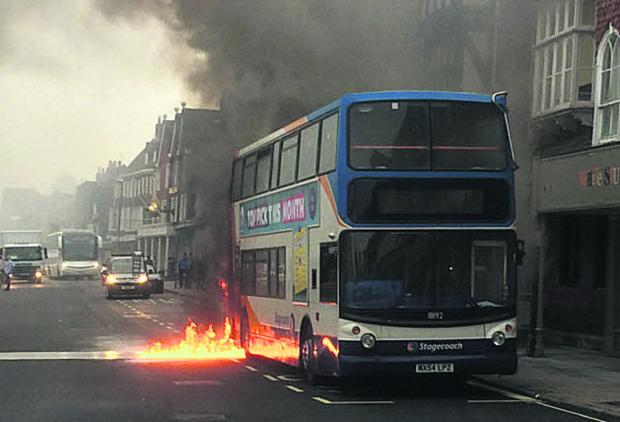 This Is Wiltshire: The bus burns in Marlborough High Street yesterday morning. Picture by Paul Shimell