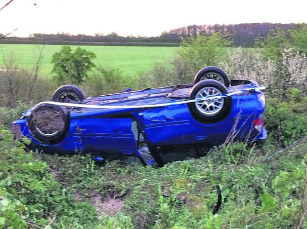 This Is Wiltshire: The overturned car in the ditch near Royal Wootton Bassett
