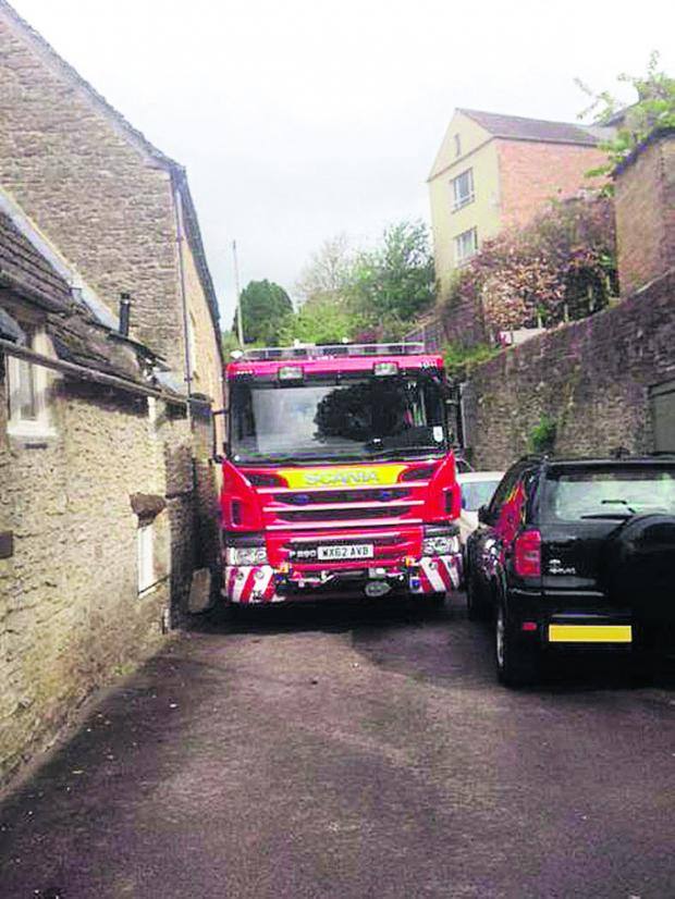 This Is Wiltshire: A fire engine attempts to squeeze past a car in a narrow lane