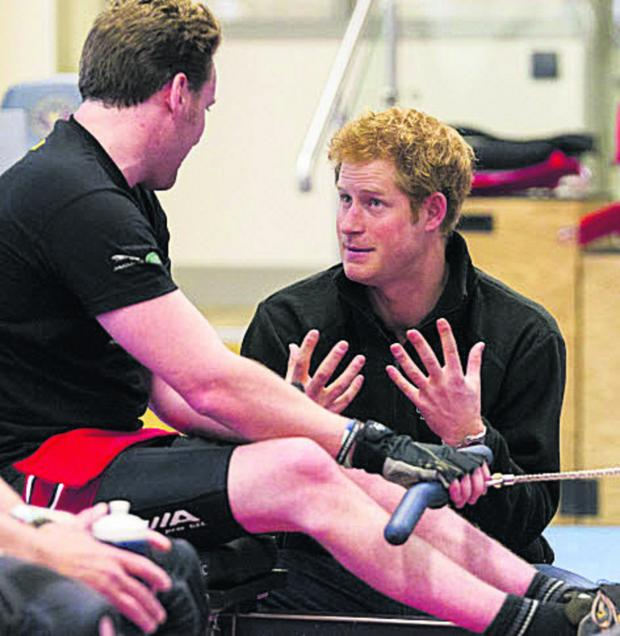 This Is Wiltshire: Prince Harry talks to veteran Jonathon Le Galloudec at the Help For Heroes gym at Tedworth House in Tidworth today. The Prince met soldiers and veterans who are hoping to be selected for the Invictus Games. Photo: Chris Ison/PA Wire