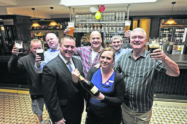 This Is Wiltshire: Bath Arms regulars Stu Eagles, Dave Humphreys, Ian Russell, Charlie McKeown and Stephen Maden join manager Catrin Ellaway and area manager Mark Howe to celebrate the pub's reopening on Tuesday