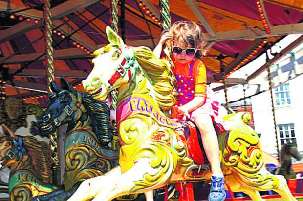 This Is Wiltshire: A youngster tries out the carousel at last year's fair