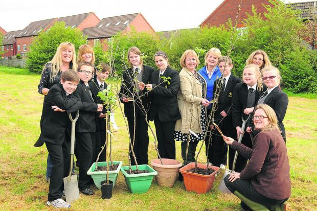 This Is Wiltshire: The chairman of the Friends of Clarendon, Juley Simmonds, back left, pupils and staff with some of the 12 apple trees which will form the orchard at the school, providing fruit for years to come