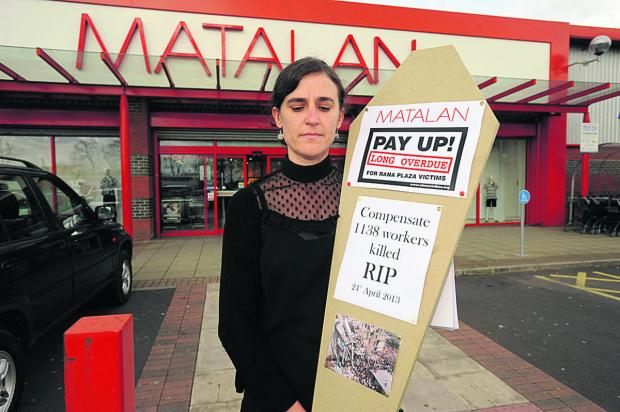 This Is Wiltshire: Liz Parker holds a memorial outside Trowbridge's Matalan for the 1,138  garment workers who died when the Rana Plaza building collapsed
