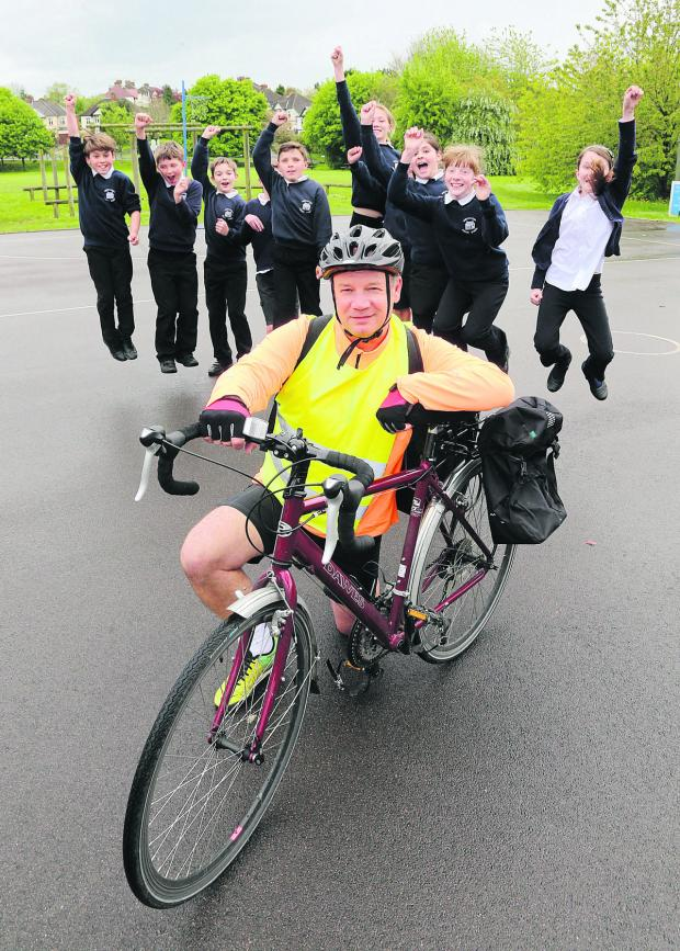 This Is Wiltshire: Jeremy Smith, who is cycling from Lands End to John O'Groats to raise money for an out door classroom for Noremarsh Primary school in Wootton Bassett, pictured with pupils. Picture: STUART HARRISON