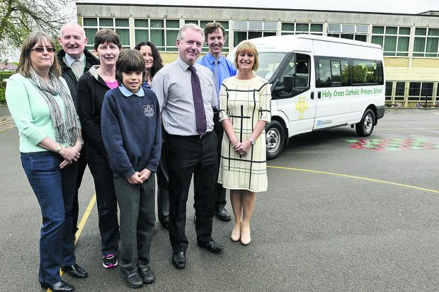 This Is Wiltshire: Holy Rood School has bought its first minibus with money raised by friends of the school. Pictured, left to right, are Mandi Morris, chair of PFA, Paul Boyles, chair of governors), Martina Haugh, treasurer of PFA, Year 5 pupil Samuel Garrett who won the D