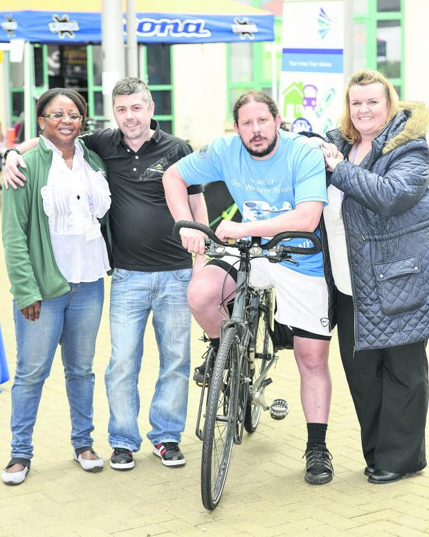 This Is Wiltshire: Daniel Cavender, second right,  is doing a last bit of fund raising before his charity ride from Rome to the Great Western Hospital. He is pictured with Sera Njie, of Swindon Travel Choices, Jason White, of Mitchell Cycles and Ellie Corcoran, of Swindon T