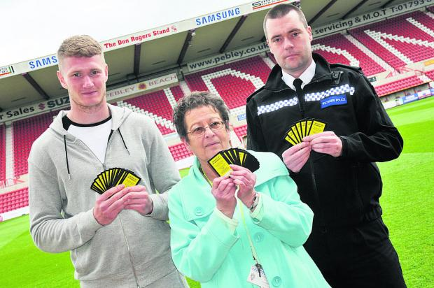 This Is Wiltshire: Swindon Town player Michael Smith, Jane Dudley of Swindon CSP and Insp Paul Saunders with the World Cup yellow cards