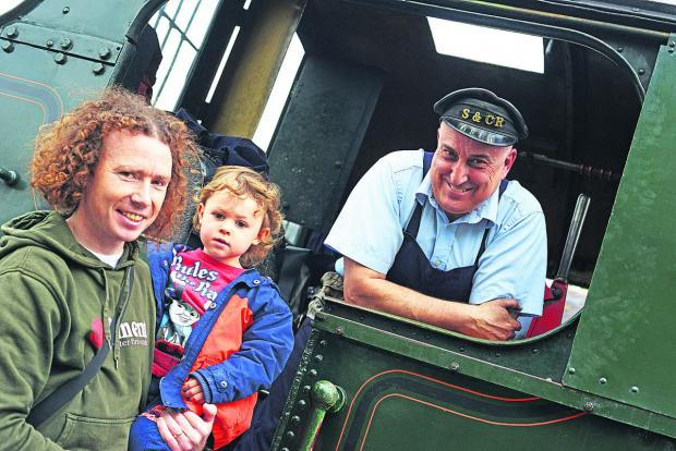 This Is Wiltshire: Blunsdon and Cricklade Railway held a children go free day. Pictured are Mike Riley with Sean and engine driver Matt Sexton