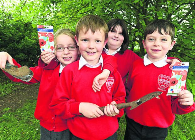 This Is Wiltshire: Ruby, Ben, Hollie and Lewis, of St Nicholas School in Bromham, ready to plant poppy seeds seeds. (DV1288) Picture by Diane Vose