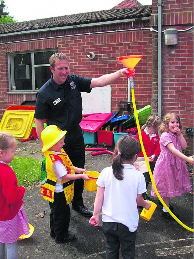 This Is Wiltshire: Fire Officer Martin Waker and Bratton Primary pupils douse a make-believe fire as part of their Health and Safety Week