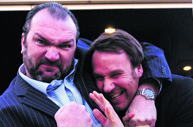 This Is Wiltshire: Neil Ruddock grapples with fellow footballer Paul Merson at a previous sporting dinner in Swindon