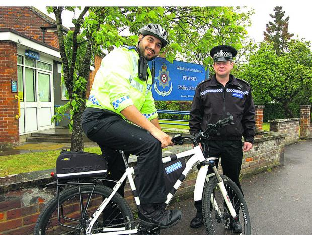 This Is Wiltshire: PCSO Joe Sadd shows Sgt Vincent Logue the new electric bike