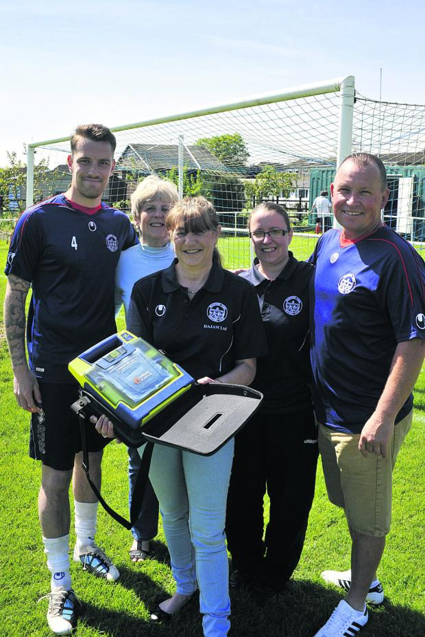 This Is Wiltshire: Bradford Town FC captain Tom Evans, treasurer Pat Stevens, secretary Nikki Akers and committee members Vikki Cumming and Adie Hiscocks with the club's first defibrillator Photo: Glenn Phillips (49377-1)