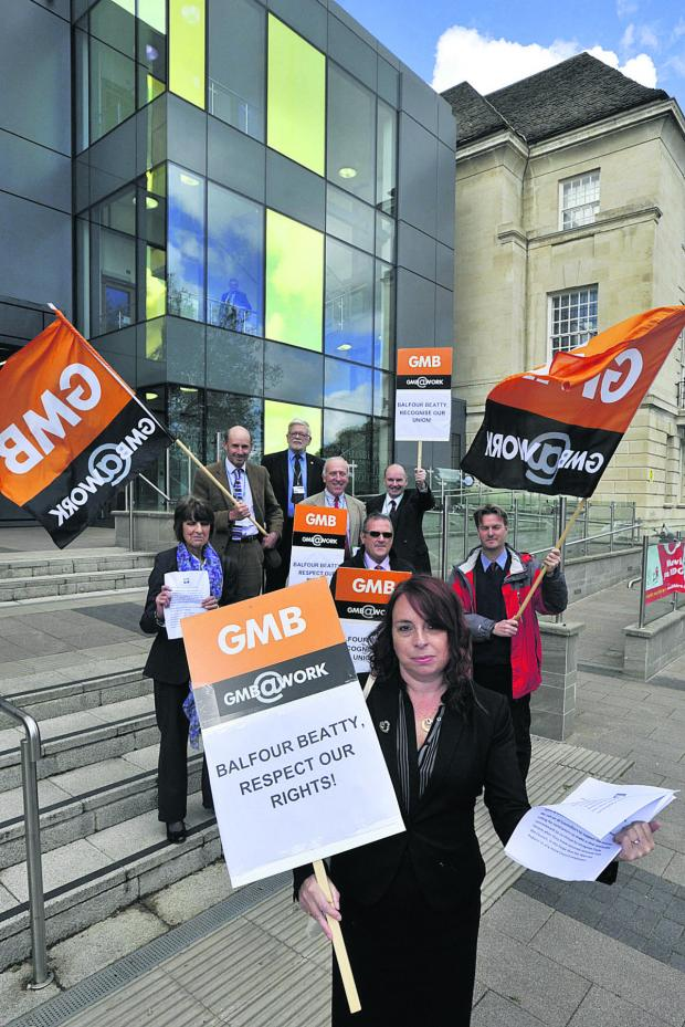 This Is Wiltshire: GMB union regional organiser Carole Vallelly, front, and supporters stage their protest outside County Hall today