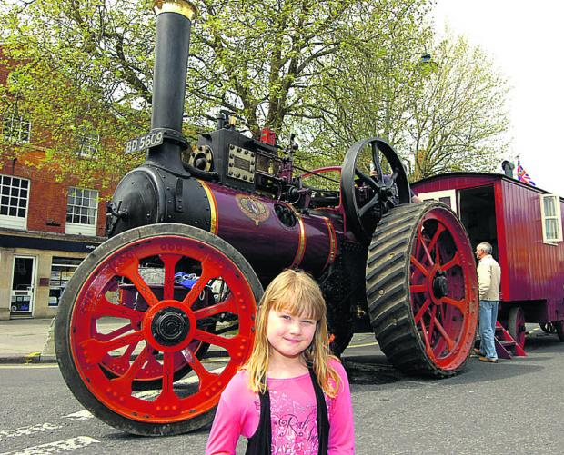 This Is Wiltshire: Abigail is pictured in front of a 1914 Marshall steam engine during the May Day Fair in Devizes. (PM232) By Paul Morris