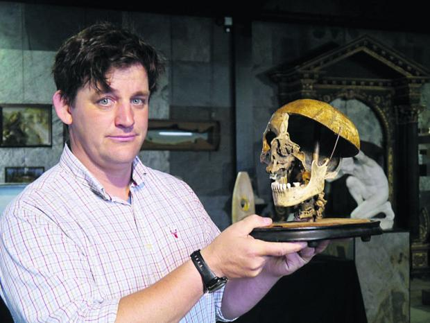 This Is Wiltshire: Specialist Rupert van der Werff with the felon's skull going under the hammer in Tuesday's natural history auction