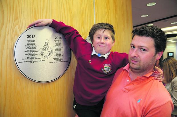 This Is Wiltshire: Morgan Sharpe, with his father Nathan, at the unveiling of this years' Pride Of Swindon plaque at the Central Library on Friday
