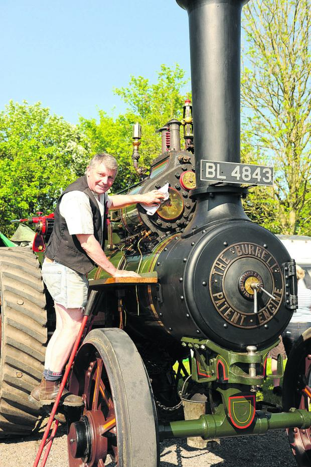 This Is Wiltshire: Colin Hatch polishes his 1901 Burrell steam engine, on show at Castle Combe