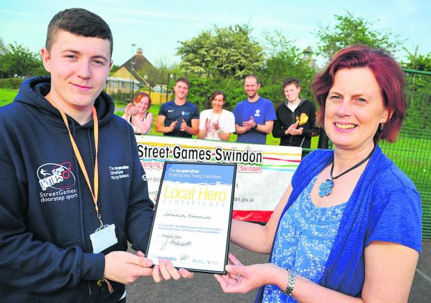 This Is Wiltshire: Nathaniel Symonds receives his Local Hero award from Gladys Barr, manager of Swindon Council Leisure Services' outreach sport and physical activity team