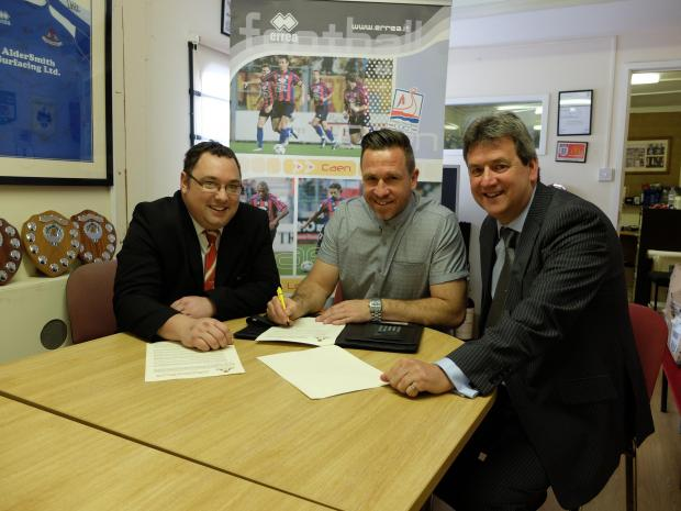 This Is Wiltshire: Frome Town boss Adrian Foster (centre) signs his new two-year deal with chairman Jeremy Alderman (right) and secretary Ian Pearce