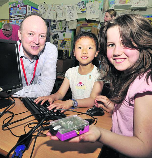 This Is Wiltshire: Emily Jacob and Liana Tiany enjoy the Raspberry Pi  jam session run by Alan O' Donohoe Hundreds of families enjoyed fascinating activities at The Mead CP School's community science and technology day