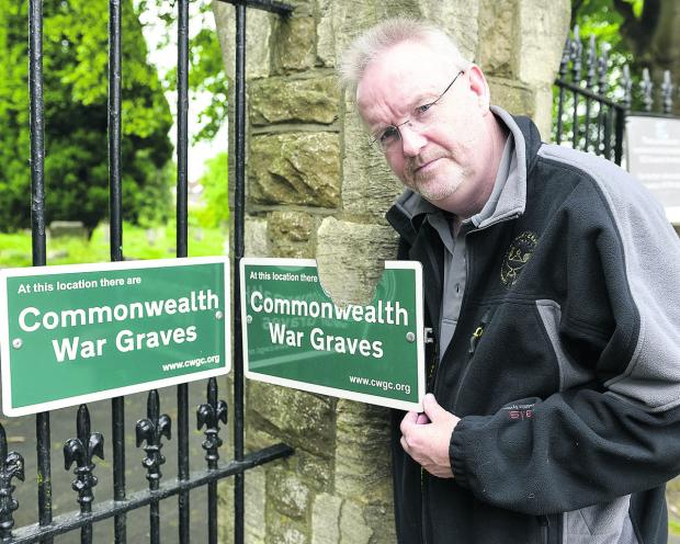 This Is Wiltshire: Andy Knowlson, Regional Supervisor West Region for the Commonwealth Wargraves Commision, which has had to replace the war graves sign on the Deacon Street Entrance to the Radnor Street Cemetery after it was vandalised