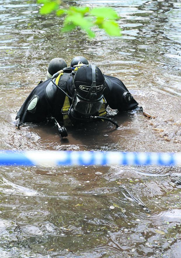 This Is Wiltshire: Divers searching a pond near Ramsbury where police have found property belonging to murdered Swindon woman Sian O'Callaghan. Picture: STUART HARRISON