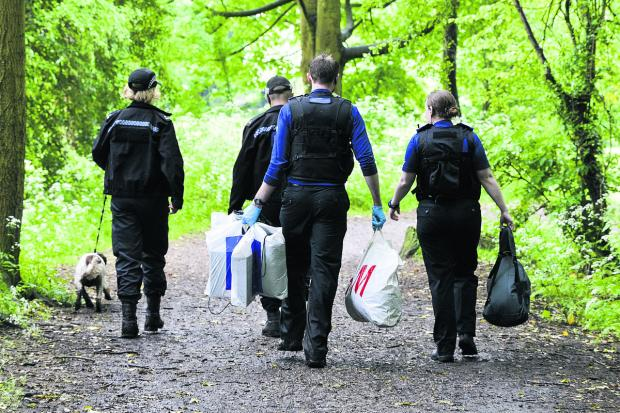 This Is Wiltshire: Police carrying evidence away from Lawn Woods in plastic sacks in after the drugs swoop yesterday. Picture: Alex Skennerton