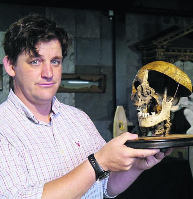 This Is Wiltshire: Specialist Rupert van der Werff with the felon's skull which sold for £2,500