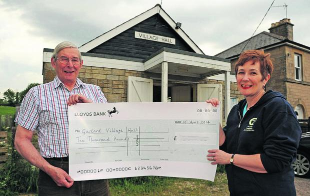 This Is Wiltshire: Gastard Village Hall secretary John Varley and treasurer Debbie Anstis with one of the cheques that topped their £20,000 target                                                       (TP48821) By Trevor Porter