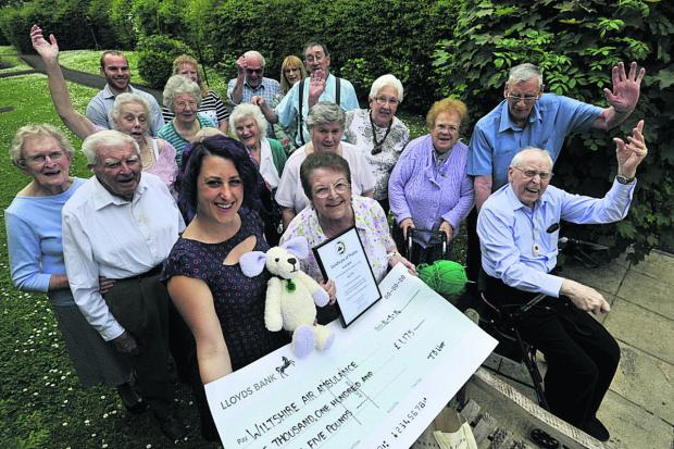 This Is Wiltshire: Fundraiser June Witt, in front of residents, gets a certificate of thanks from Rebecca de la Bedoyere