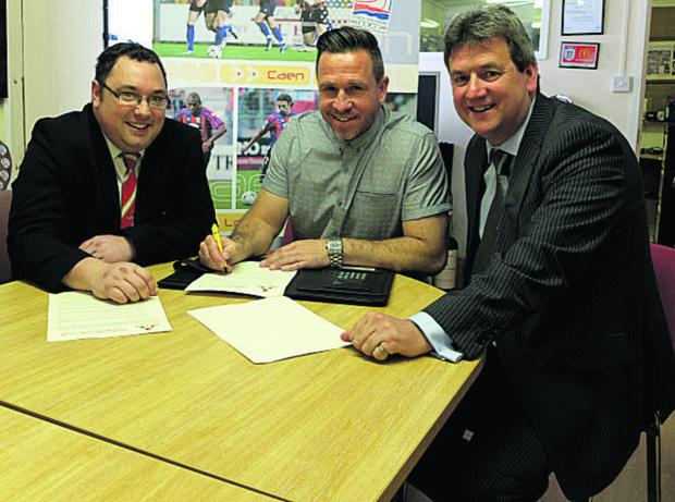 This Is Wiltshire: Adrian Foster signing his contract with chairman Jeremy Alderman (right) and club secretary Ian Pearce (left)