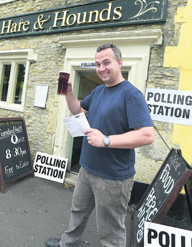 This Is Wiltshire: Mark Foster, landlord of the Hare and Hounds in Corsham, with a pint and polling card today
