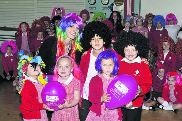 This Is Wiltshire: Gemma Hector of Apple a Day Supply, which organised the Wig Wednesday charity event in aid of CLIC Sargent, with Betty, Brooke, Tilly, Mete, Bradley and other pupils at Walwayne Court Primary School