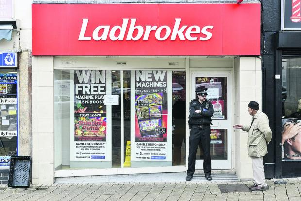 This Is Wiltshire: A police officer stands guard outside Ladbrokes in Regent Street after the robbery in March