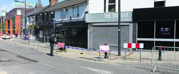 This Is Wiltshire: Officers cordoned off the area after the fight in Regent Circus in the early hours of Sunday