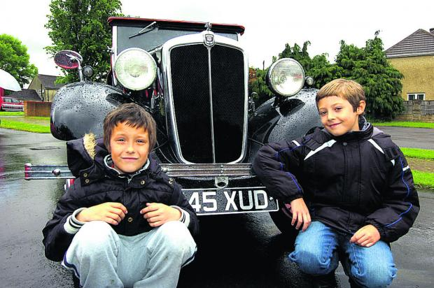 This Is Wiltshire: Louie and Cai with a Morris 8 at the classic car show held at Lady Evangelical Church in Chippenham