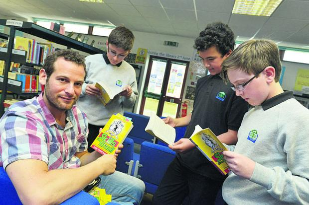 This Is Wiltshire: Football author Dan Freedman shows  pupils at Bradon Forest School his book, Skills From Brazil