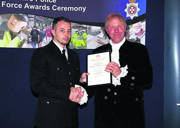 This Is Wiltshire: PC Tim Stevens receives his award from High Sheriff of Wiltshire Mr Peter Addington