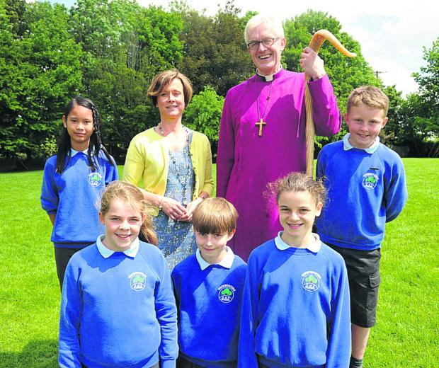 This Is Wiltshire: The Bishop of Ramsbury is welcomed by headteacher Sarah Brewis and pupils, back from left, Amy and Robert; front, Lily, Liam and Georgie