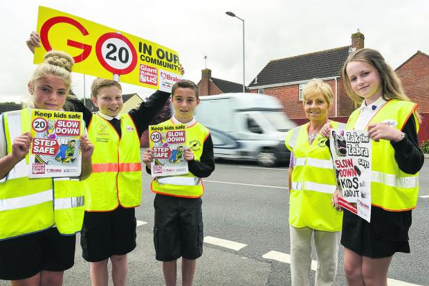 This Is Wiltshire: Pupils from Haydonleigh Primary School take to the streets to promote road safety. From left, Eve Hackman, Cameron Clements, Jarvey Richards, senior teaching assistant Debbie Yockney and  Hattie Bulpitt